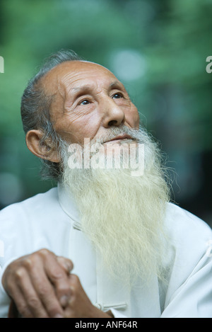 Elderly man in traditional Chinese clothing, looking up, portrait - Stock Photo
