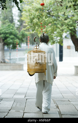 Elderly man in traditional Chinese clothing, carrying bird cage over back, rear view - Stock Photo