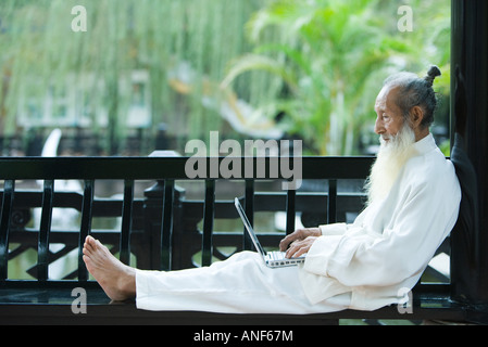 Elderly man in traditional Chinese clothing, barefoot, using laptop - Stock Photo