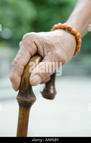 Elderly man holding cane, close-up of hand - Stock Photo