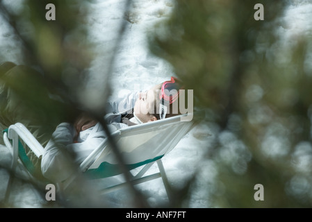 Young skier resting in chair on snow, blurred branches in foreground - Stock Photo
