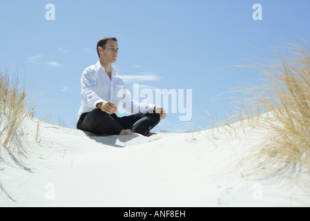 Businessman sitting on sand dune, meditating - Stock Photo