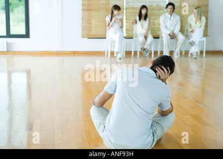 Man sitting on floor, facing group sitting in chairs - Stock Photo
