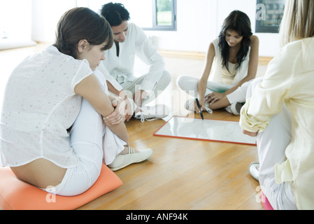 Adults sitting on cushions on floor, one woman drawing on drywipe board - Stock Photo
