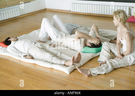 Alternative therapy session, three adults lying side by side while therapist sits nearby - Stock Photo