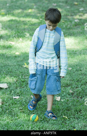Boy wearing backpack, poised to kick ball - Stock Photo