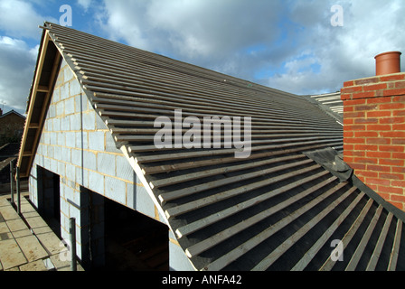 Detached house under construction, roof works including gable end felt battens and general preparation for plain - Stock Photo