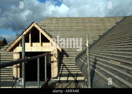 Detached house under construction, roof works including gable end dormer window, felt and battens ready for plain - Stock Photo