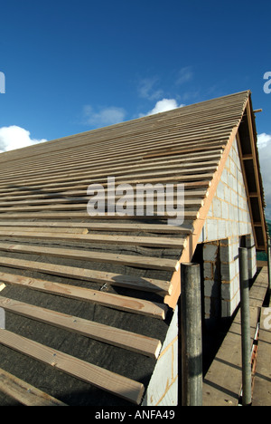 Detached house under construction, roof works including gable end, felt, battens and general preparation for plain - Stock Photo