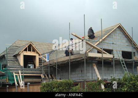 Detached house under construction roofers fixing tile battens to receive plain tiles - Stock Photo
