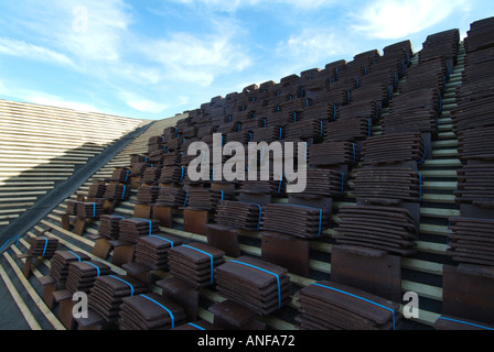 Detached house under construction at roof stage with plain tiles stacked on tile battens awaiting fixing - Stock Photo