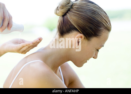 Woman having back massage, massage therapist pouring oil into palm of hand - Stock Photo