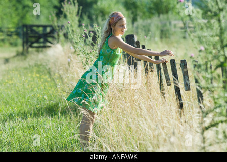Young woman leaning against fence in rural field, smiling - Stock Photo
