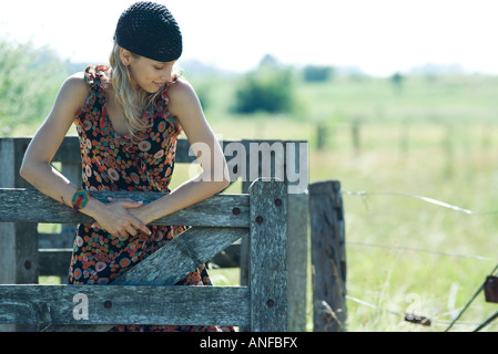 Young woman holding on to wooden fence, looking away - Stock Photo