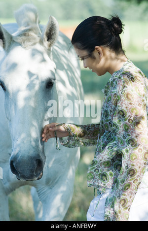 Young woman touching horse, side view - Stock Photo