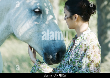 Young woman touching horse, side view, close-up - Stock Photo