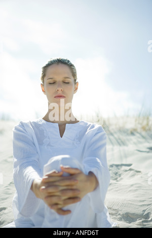 Young woman sitting on dune with eyes closed - Stock Photo