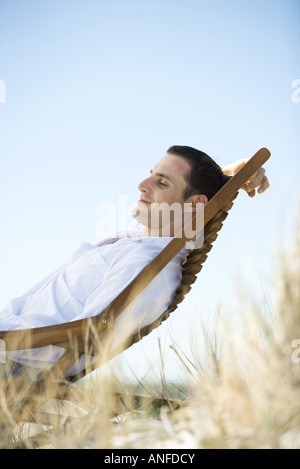 Young man sitting in deck chair - Stock Photo