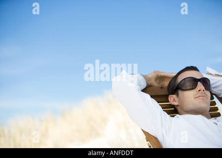 Young man sitting in deck chair, wearing sunglasses - Stock Photo