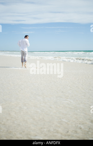 Young man running through surf on beach, rear view - Stock Photo