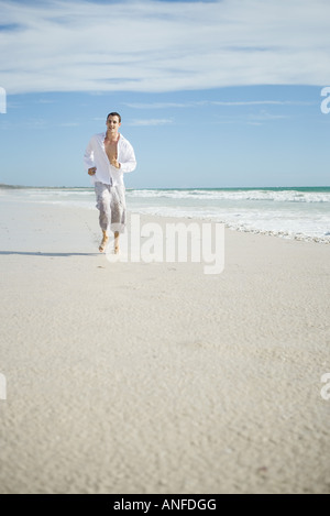 Young man running through surf on beach, front view - Stock Photo