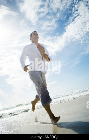 Young man running through surf on beach, low angle view, full length - Stock Photo