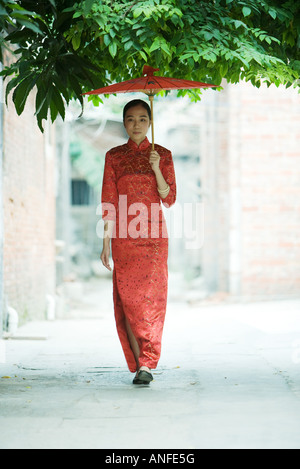 Young woman wearing traditional Chinese clothing, walking with parasol