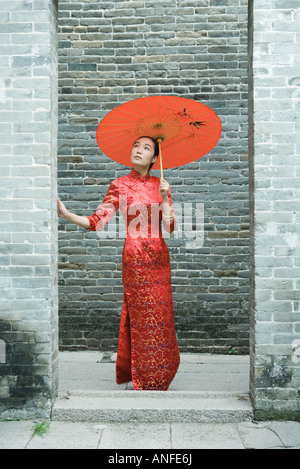 Young woman wearing traditional Chinese clothing, standing with parasol, full length - Stock Photo