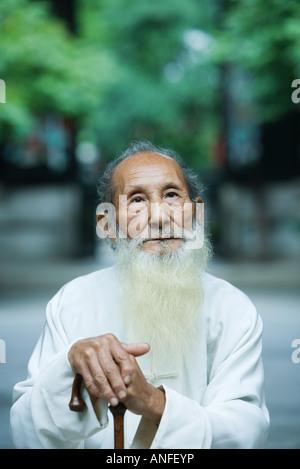 Elderly man wearing traditional Chinese clothing, holding cane - Stock Photo