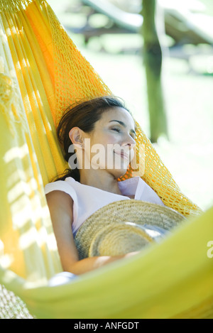 Woman resting in hammock, holding straw hat - Stock Photo
