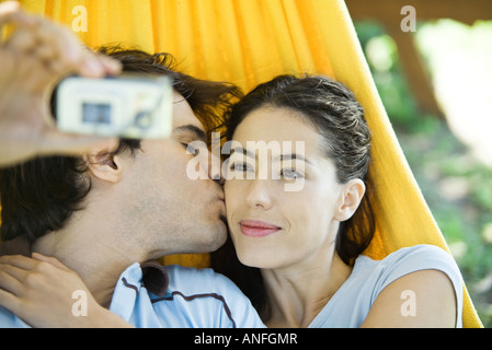 Young couple lying in hammock, taking photo of selves with digital camera - Stock Photo