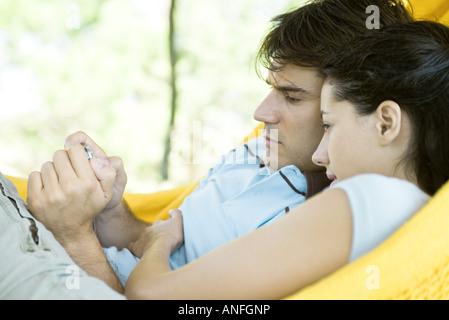Young couple lying in hammock, using digital camera - Stock Photo
