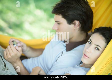 Young couple lying in hammock, using digital camera, woman looking at camera - Stock Photo