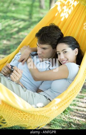 Young couple lying in hammock, using digital camera, woman smiling at camera - Stock Photo