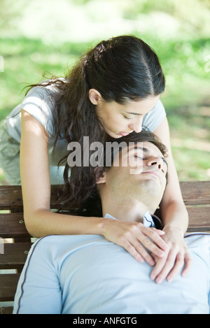 Young couple, man sleeping on bench while woman puts arms around him from behind - Stock Photo