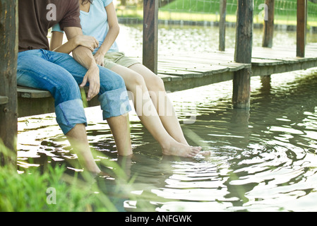 Couple sitting on dock, dangling legs in water, chest down - Stock Photo