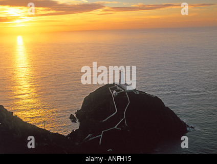 HOLYHEAD ISLE OF ANGLESEY NORTH WALES UK The sun sets behind the South Stack Lighthouse built in 1809 on Ynys Lawd - Stock Photo