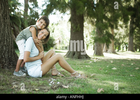 Mother and son sitting outdoors, boy hugging woman from behind - Stock Photo
