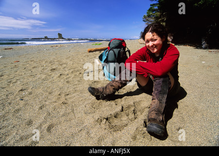 A Young Woman (20-25) takes a break from hiking along a beach section of the West Coast Trail near Carmanah Creek - Stock Photo