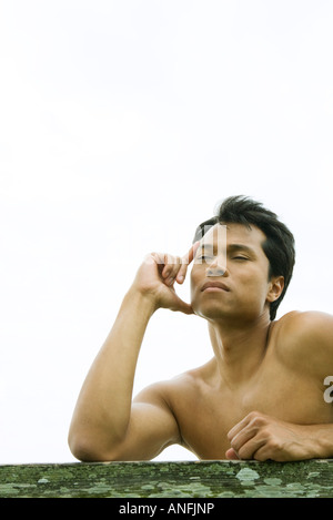 Man leaning on rail, holding head, eyes half closed - Stock Photo