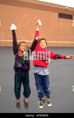Students age 11 flying paper airplanes at recess during summer school. Holland School Minneapolis Minnesota USA - Stock Photo