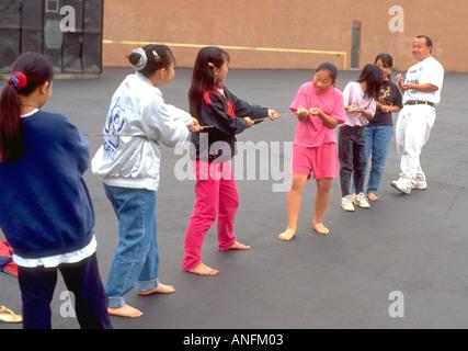 Asian American girls age 12 playing tug of war at summer school with teacher. Holland School Minneapolis Minnesota - Stock Photo
