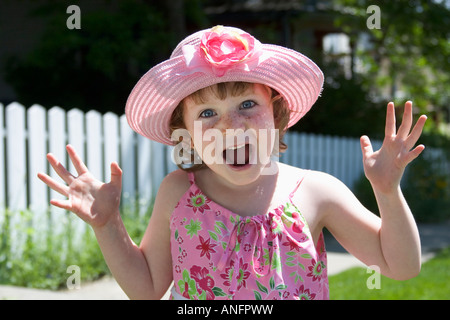 5 year old girl with sundress and hat showing surprise, canada. - Stock Photo