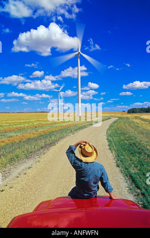 Man on truck viewing wind turbines in canola field, near St. Leon, Manitoba, Canada. - Stock Photo