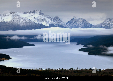 Glacial lake with fog forming in valley and Mt. Moore in distance, Tatlayoko Lake, British Columbia, Canada. - Stock Photo