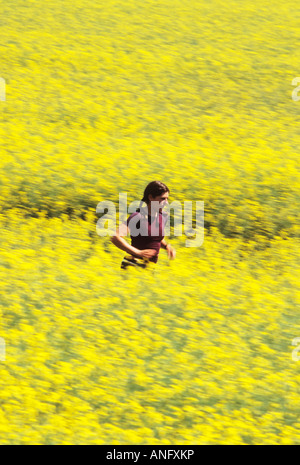 a young athletic woman running through a field of beautiful yellow flowers in bloom, Calgary, Alberta, Canada. - Stock Photo