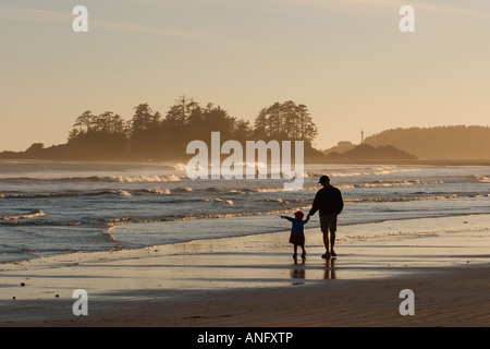 Father & daughter walk along beach, Chesterman Beach near Tofino, Vancouver Island, British Columbia, Canada. - Stock Photo