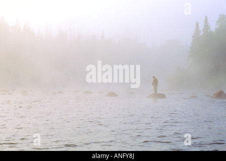 Salmon fishing in fog on the Upper Humber River, Newfoundland, Canada. - Stock Photo