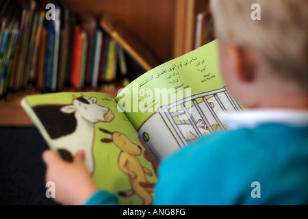 A child reading a book in different languages in a school in the UK - Stock Photo