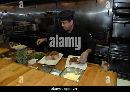 Chef prepares porterhouse steak at Ricardo Steak House in East Harlem in NYC - Stock Photo